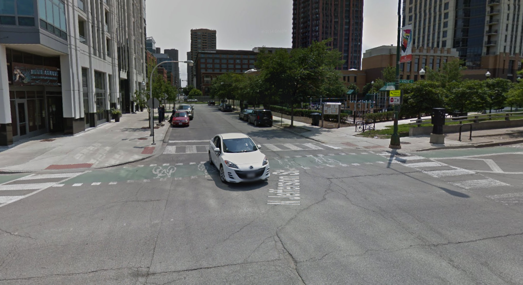 Kinzie runs east-west, side to side in this Google Street View image. The ideal viewing angle between a motorist and bicyclist is 90 degrees, which is possible for the eastbound cyclist (from right to left) and the northbound motorist (pictured, in the white car). The eastbound motorist turning onto southbound Jefferson has an acute view angle to the cyclist and motorists typically believe they can make the right turn before it could possible harm the cyclist. Making the street one-way would mitigate this right-hook problem.